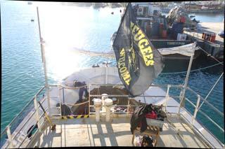 das hintere Deck der LIFELINE im Hafen von Malta von oben fotografiert, eine Person macht Reparaturarbeiten, im Vordergrund eine Refugees-Welcome-Fahne
