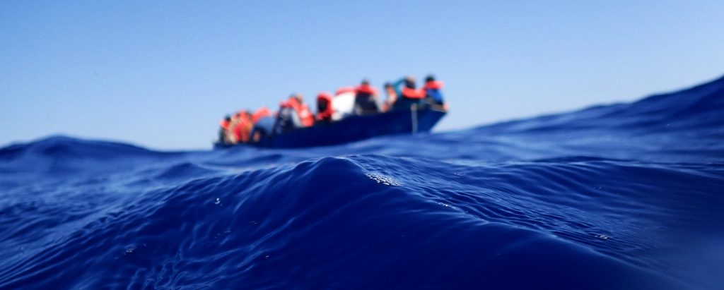 In the foreground a blue wave on the Mediterranean Sea, in the background in the distance a life boat with people wearing red life jackets