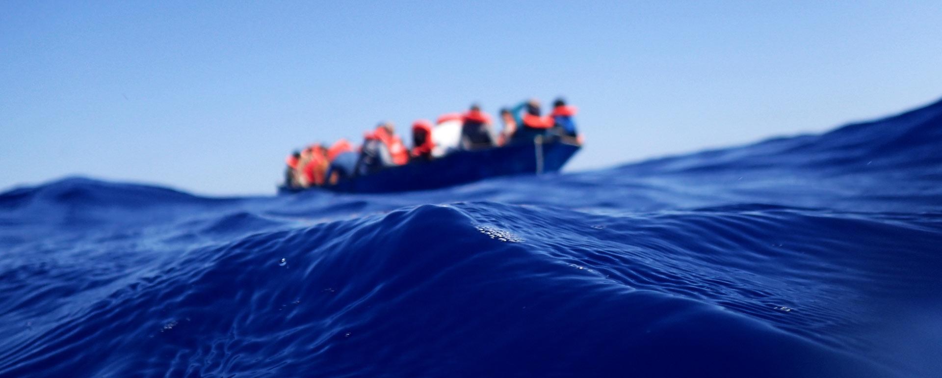 Im Vordergrund eine blaue Welle auf dem Mittelmeer, im Hintergrund in der Ferne ein Rettungsboot mit Menschen, die rote Schwimmwesten tragen