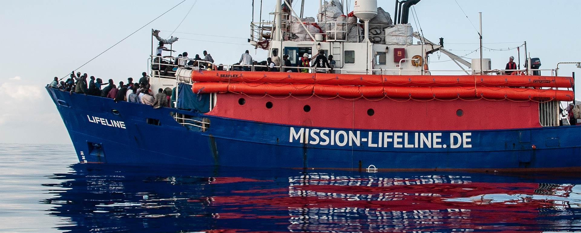 Schiff Lifeline von der Seite, mit mehreren Menschen an Bord, die an Deck stehen. An der Seite Schriftzug Mission Lifeline. Spiegelbild reflektiert auf ruhiger See