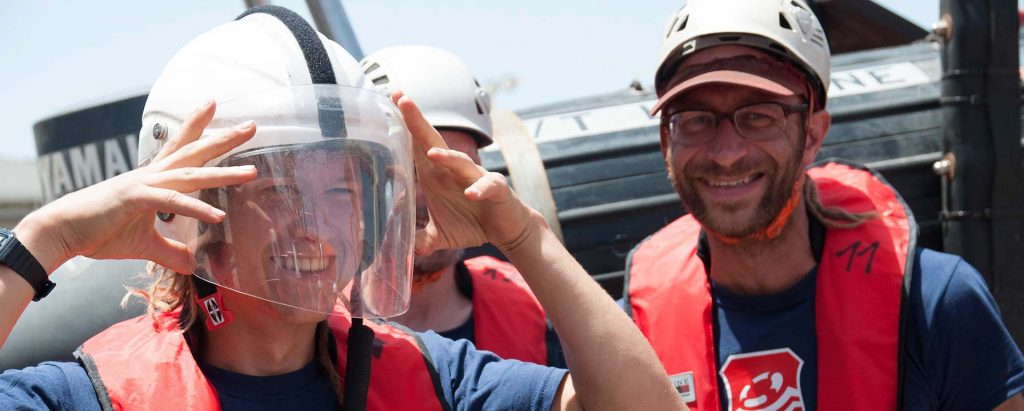 Foto von zwei Lifeline-Crewmitgliedern, die in die Kamera lächeln. Eine hat einen Helm auf und hält die Hände zum Helm hoch