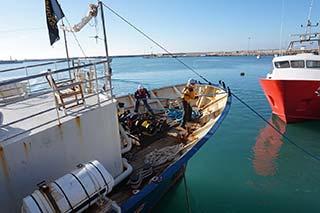 Lifeline im Hafen von Malta, zwei Menschen arbeiten an Deck für Reparaturen, im Hintergrund Meer