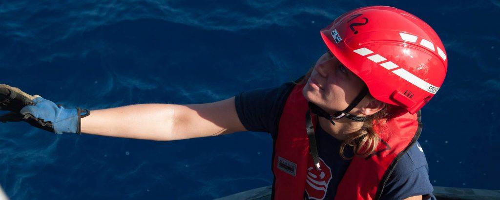 Lifeline-Crewmitglied auf Boot in Nahaufnahme, im Hintergrund das Meer, hat Helm und Handschuhe an und schaut nach oben