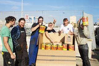 Team der Lifeline steht um ein Paket mit Farbeimern herum, halten Farbeimer in die Luft und lächeln in die Kamera