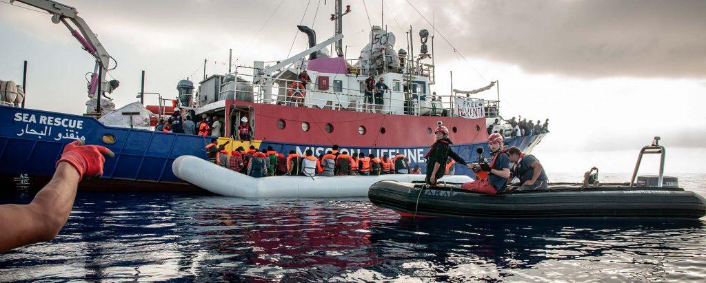 Blick auf die Lifeline auf offener See von der Seite. Ein Boot mit geretteten Menschen legt gerade an und wird in Empfang genommen, um die Lifeline zu betreten. Im Vordergrund ein kleineres Boot mit Crewmitgliedern. Himmel bewölkt. An der Lifeline hängt ein Transparent mit der Aufschrift Free Iuventa