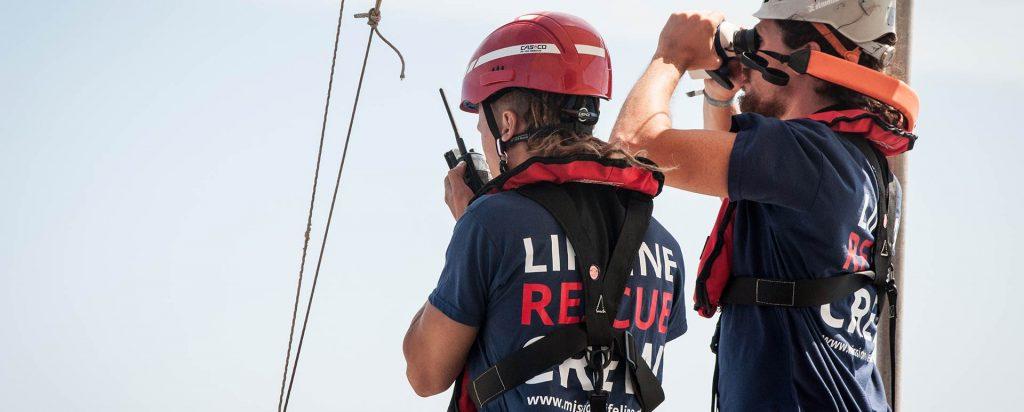 Zwei Lifeline-Crewmitlieder von hinten, die Rettungswesten, Helme und Lifeline-T-Shirts tragen. Eine Person spricht in ein Funkgerät, die andere Person schaut durch Ferngläser