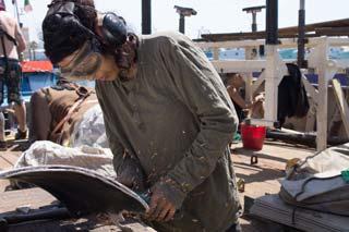 auf dem Deck der LIFELINE, eine Person schweißt Metall, trägt Sicherheitsbrille