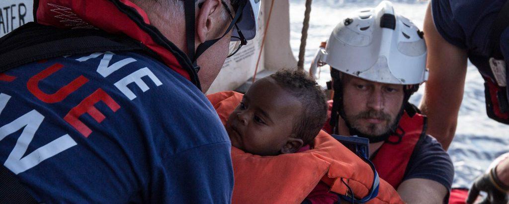 Lifeline-Crewmitglieder reichen ein gerettetes Baby in Schwimmwesten weiter, um es auf das Schiff zu tragen