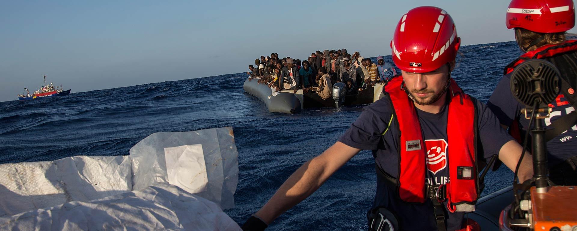Lifeline-Crew im Einsatz auf offener See. Im Hintergrund links das Schiff Lifeline, in der Mitte ein Boot mit geretteten Menschen. Im Vordergrund zwei Lifeline-Crewmitglieder in der Nahaufnahme, die Rettungswesten und Helme tragen