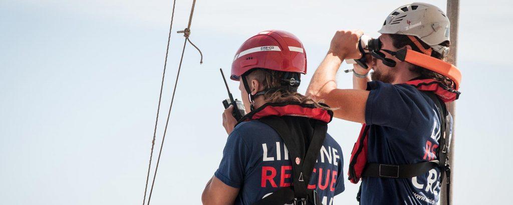 Das Bild zeigt zwei Crewmitglieder von Mission Lifeline an Deck des Schiffs von hinten. Eine Person schaut durch ein Fernglas, die andere spricht in ein Funkgerät. Im Hintergrund das Meer