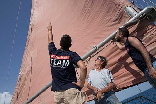 Crewmitglieder inspizieren die Segel auf einer Yacht