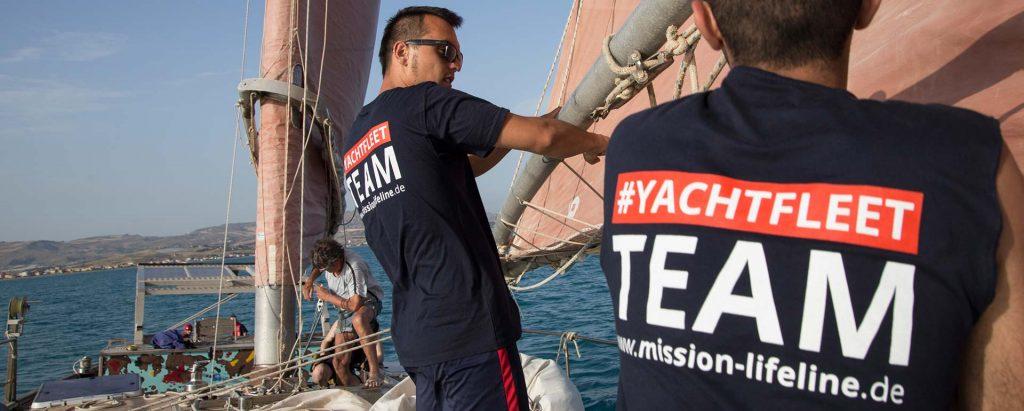 Crewmitglieder hissen die Segel