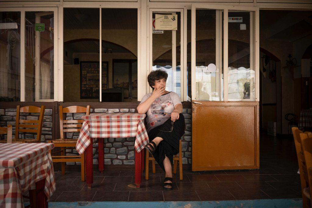 Voula sitzt rauchend vor ihrer Taverne
